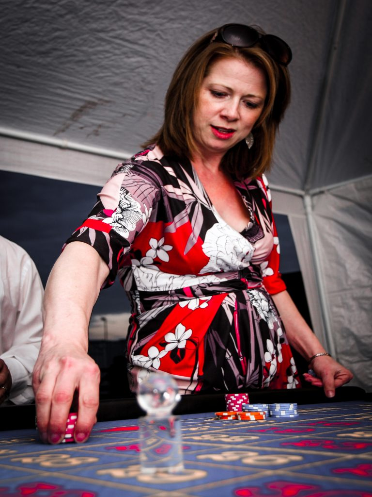 Lady placing chips down at Roulette table.