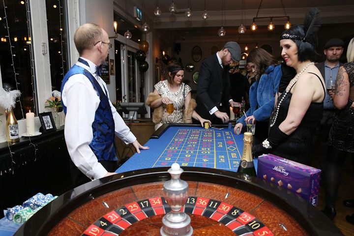 roulette table hire with dealer and guests at the table.