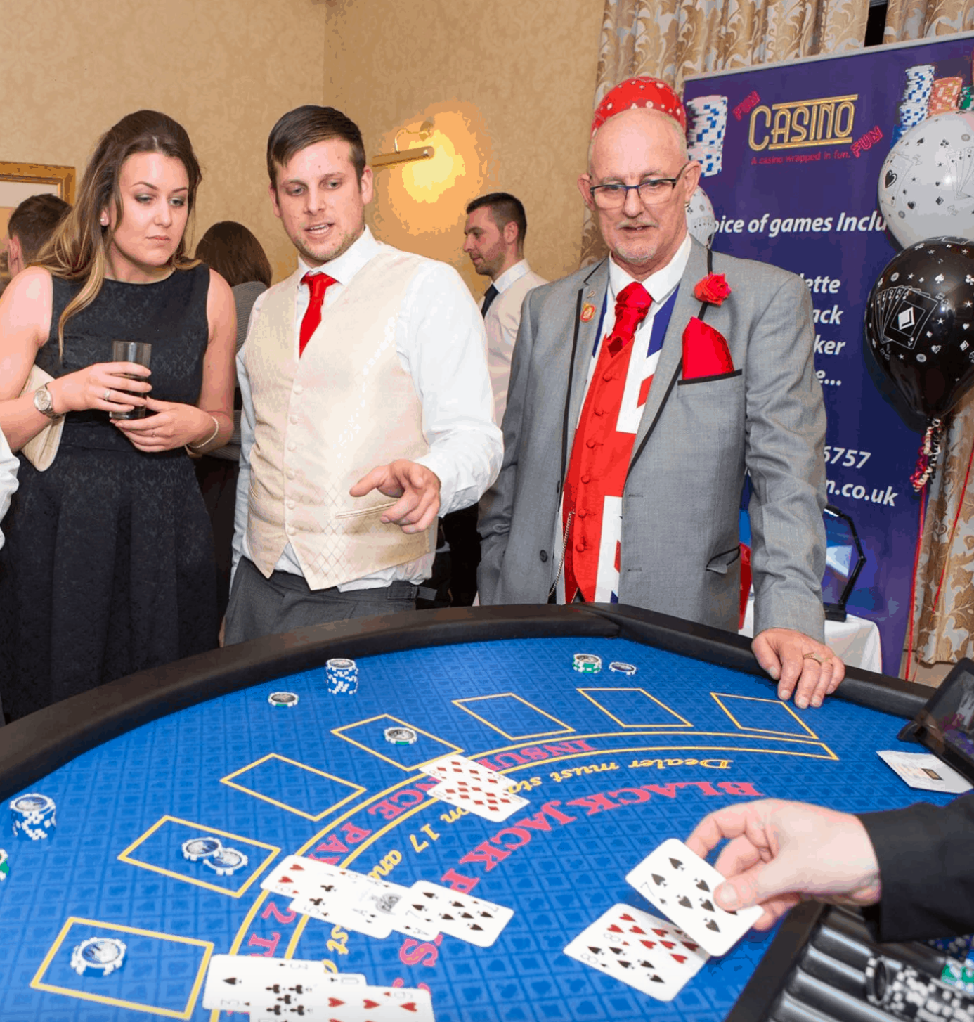 People wearing party clothes stood at a Blackjack table.