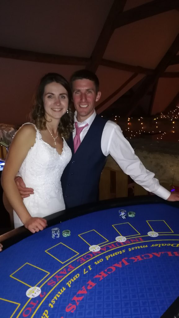 Happy recently married couple stood at Blackjack table.