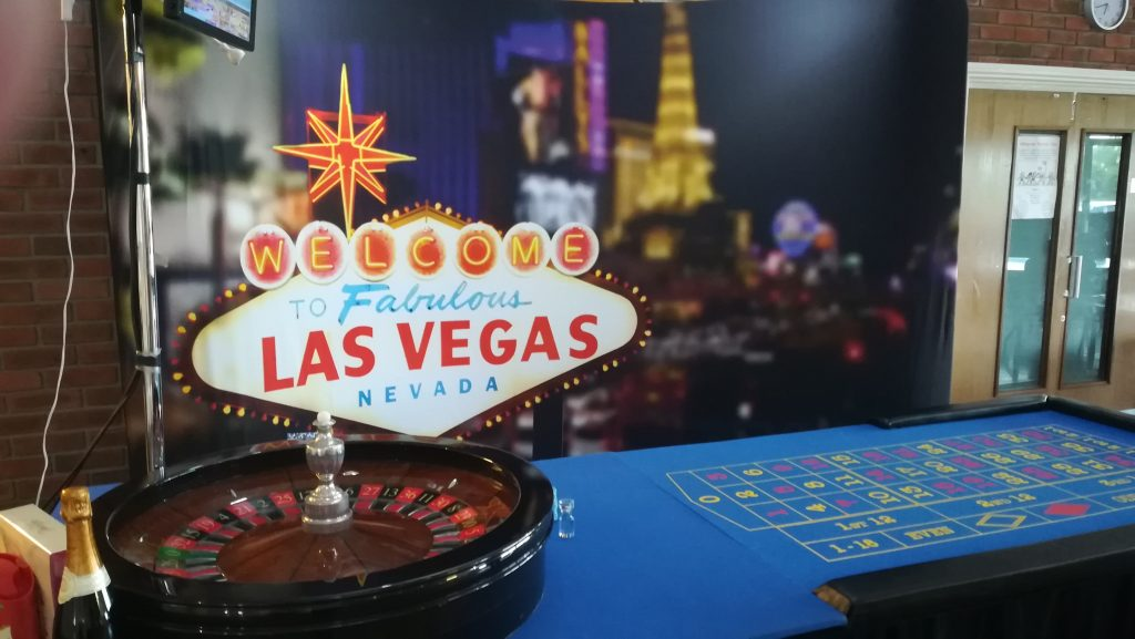 Roulette table in front of a Las Vegas backdrop.